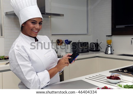 Happy chef cooking in kitchen and typing sms - stock photo