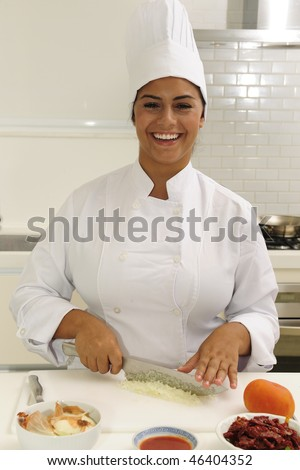 Happy chef cutting onions in a modern kitchen - stock photo