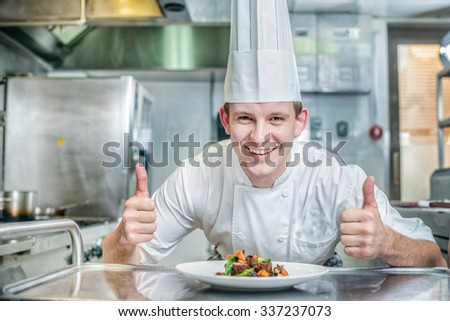 Happy Chef standing over the dish and showing thumbs up. Young chef preparing a delicious meal in the kitchen of the restaurant - stock photo