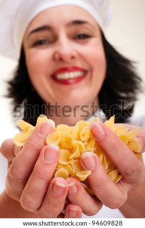 Happy chef woman holding macaroni handful in hands - stock photo