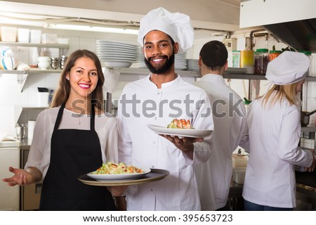 Happy chefs and young nippy in apron working at restaurant kitchen