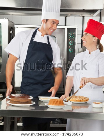 Happy chefs looking at each other while preparing sweet dishes in commercial kitchen - stock photo