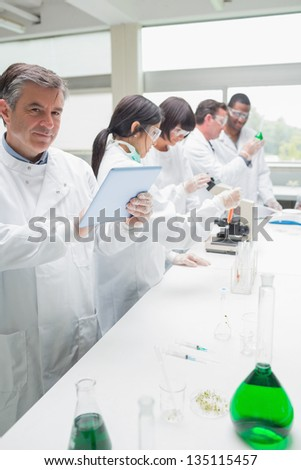 Happy chemist using tablet pc in busy lab - stock photo