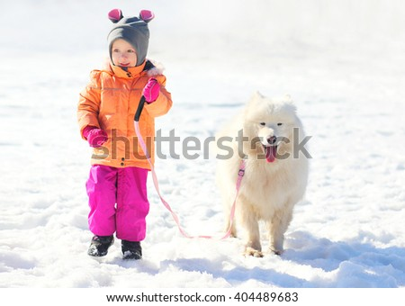 Happy child and white Samoyed dog walking together in winter day - stock photo