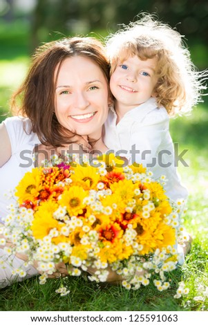 Happy child and woman with bouquet of spring flowers lying on green grass. Mother`s day concept - stock photo
