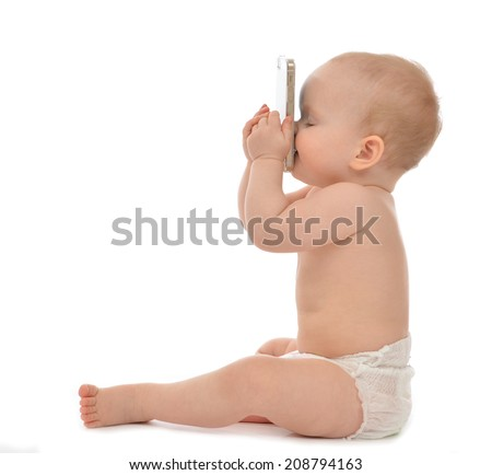 Happy child baby toddler sitting smiling kissing mobile cellphone on a white background - stock photo