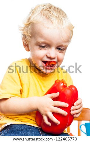 Happy child boy biting red sweet pepper, isolated on white background. - stock photo
