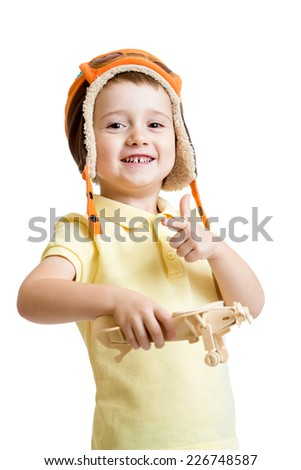 happy child boy dressed pilot hat and playing with wooden airplane toy - stock photo