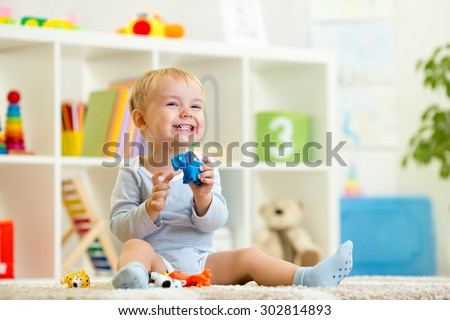 happy child boy holds elefant toy sitting on floor in nursery - stock photo