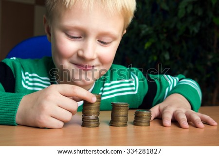 Happy child (boy, kid, teen) making stacks of coins on the table. Children and money concept. - stock photo