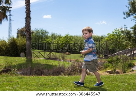 Happy child boy walking in the park during sunny summer day. - stock photo