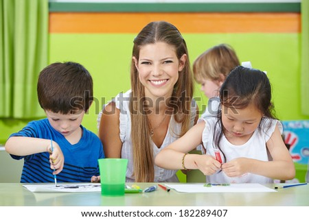 Happy child care worker with children drawing in a kindergarten - stock photo