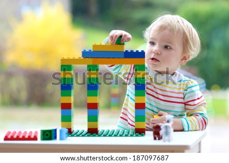 Happy child, cute blonde toddler girl building house from plastic blocks sitting next to a big window indoors at home or kindergarten - stock photo