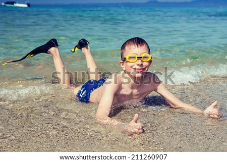 Happy child diver in swimware lying on beach at mediterranean sea smiling showing thumbs up - stock photo