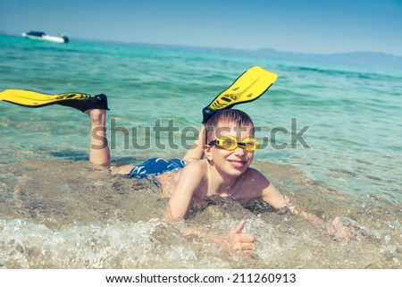 Happy child diver in swimware lying on beach in sea smiling showing thumbs up - stock photo
