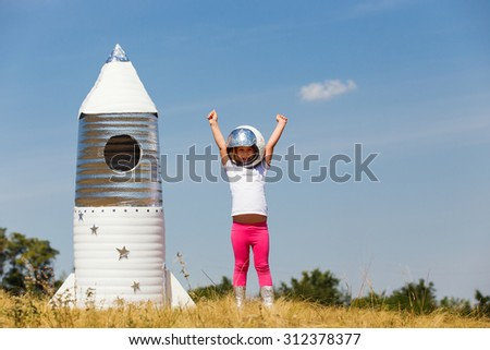 Happy child dressed in an astronaut costume playing with hand made rocket. Summer outdoor - stock photo