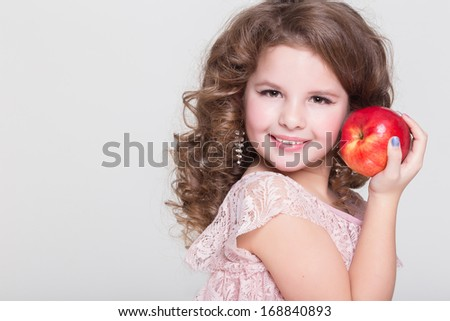 Happy child eating apples healthy organic food, little girl with red apple, isolated. Beautiful baby girl eating fruit. Kid hold red apple. Studio. white background.  - stock photo