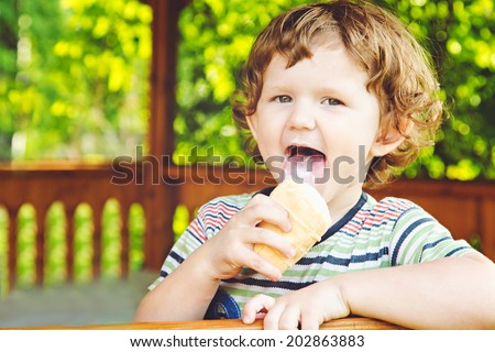 Happy child eating ice-cream in summer park. - stock photo