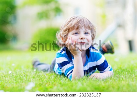 Happy child enjoying on grass field and dreaming. Cute blond boy with blue eyes on warm sunny summer day, outdoors. - stock photo