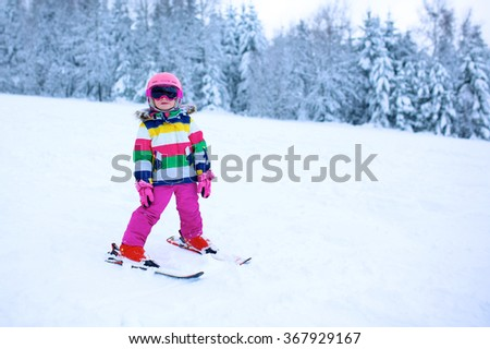 Happy child enjoying vacation in Alpine resort. Little girl skiing in mountains. Active sportive toddler wearing helmet and glasses learning to ski. Winter sport for family. Skier racing in snow. - stock photo