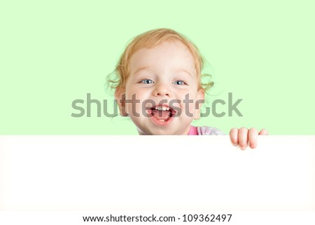 Happy child face behind blank advertising banner. Banner and green background are easily expandable in any direction. - stock photo