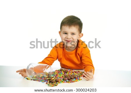 Happy child ( four years old little boy ) eating sweets, isolated on white background. - stock photo
