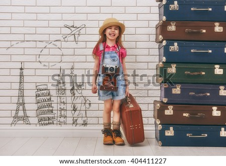 happy child girl against a white brick wall. girl having suitcases and dreaming of traveling. - stock photo