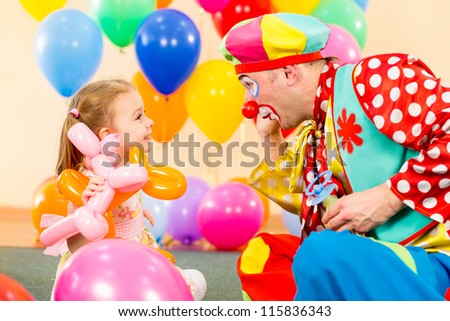 happy child girl and clown playing on birthday party - stock photo