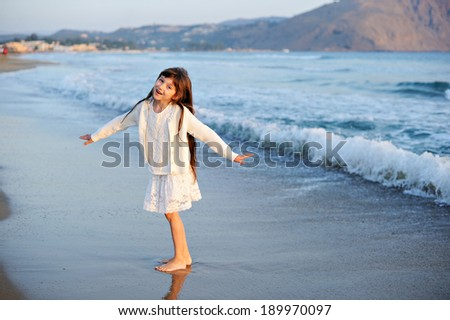 Happy child girl enjoying her beach vacation - stock photo