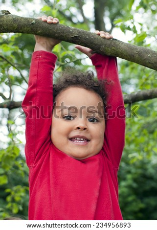 Happy child girl hanging on a tree branch - stock photo