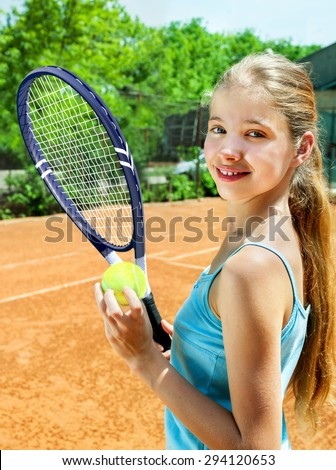 Happy child girl holding  racket and ball on  brown tennis court. Green tree on background. - stock photo