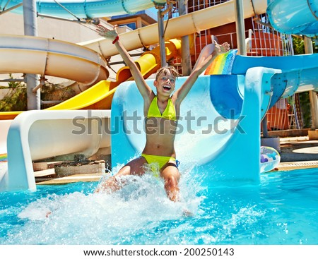 Happy child girl in bikini sliding water park. - stock photo