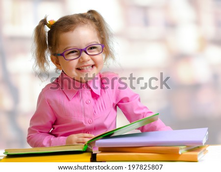 Happy child girl in eyeglasses reading books sitting at table - stock photo