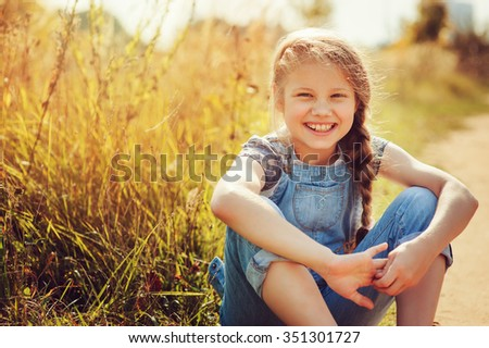 happy child girl in jeans overall playing on sunny field, summer outdoor lifestyle, cozy mood - stock photo