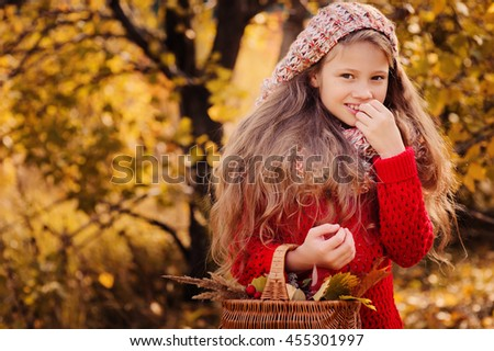 happy child girl in knitted scarf and sweater with basket on autumn walk in forest eating apples. Fall harvest, cozy mood. - stock photo
