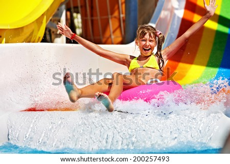 Happy child girl in yellow bikini sliding water park. - stock photo