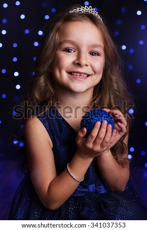 Happy child girl is holding blue Christmas tree ball in hands over background scene with lights, New years - stock photo