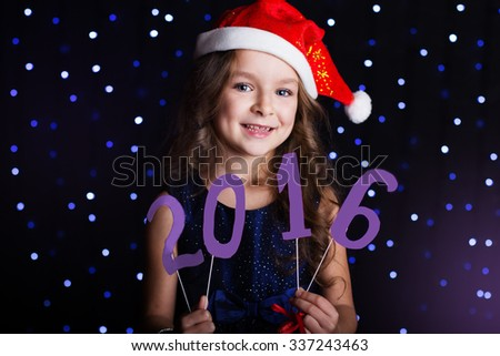 Happy child girl is wearing santa hat holding numbers 2016 in hands in a studio over background scene with blue lights for a holiday concept. - stock photo