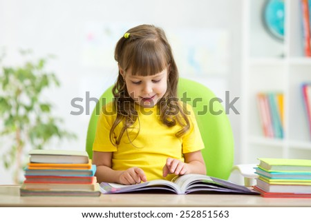 Happy child girl learning to read in nursery - stock photo