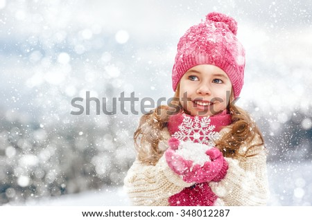 happy child girl plaing on a snowy winter walk - stock photo