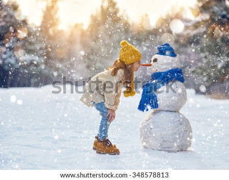 happy child girl plaing with a snowman on a snowy winter walk - stock photo