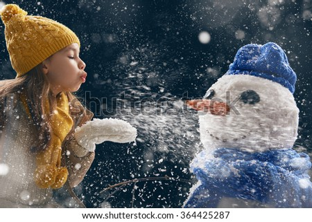 happy child girl plaing with a snowman on a snowy winter walk. Little girl enjoys the game. Child girl playing outdoors in snow. Outdoor fun for winter vacation. - stock photo