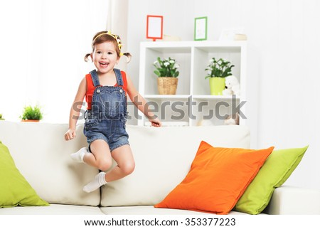 happy child girl playing and jumping on the couch at home - stock photo