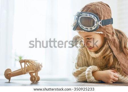 happy child girl playing with toy airplane. the dream of becoming a pilot - stock photo