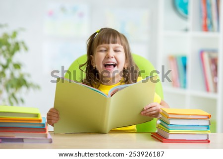 Happy child girl with opened book at home - stock photo