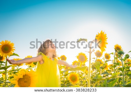 Happy child having fun in spring field against blue sky background. Freedom concept - stock photo