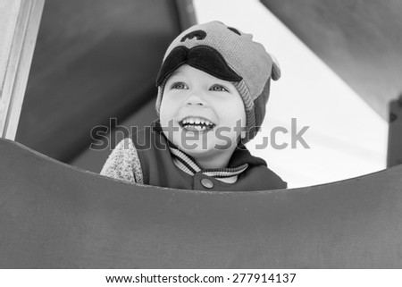 happy child having fun on the playground in sunny weather ( black and white ) - stock photo