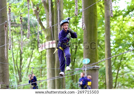 Happy child, healthy teenager school boy enjoying group friends activity in a climbing adventure park on a summer day - stock photo