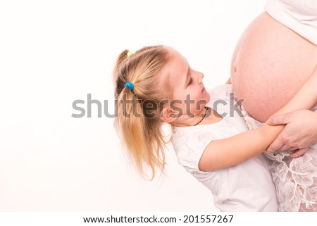 Happy child holding belly of pregnant woman isolated on white background - stock photo