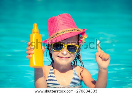 Happy child holding sunscreen lotion in hand. Summer vacations concept - stock photo